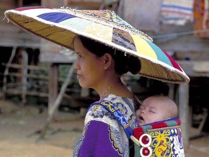 Una mujer lleva a su bebé a la espalda en Indonesia.
