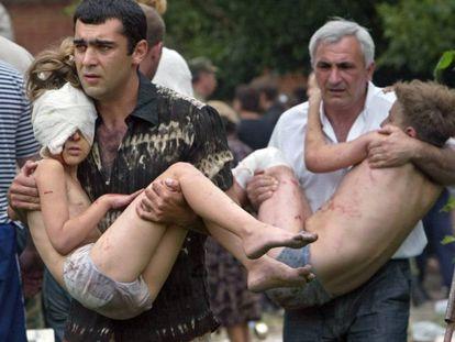 Dos hombres llevan en brazos a sendos niños liberados tras el asalto de las fuerzas rusas en Beslan, en 2004 (archivo).