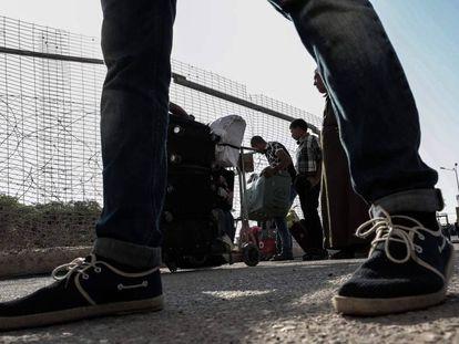 Un grupo de palestinos espera para recibir permisos y cruzar a Egipto.