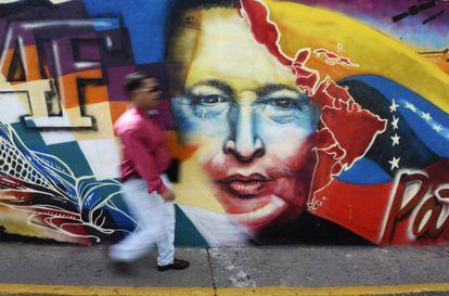 Un hombre camina frente a un mural dedicado a Chávez en Caracas.