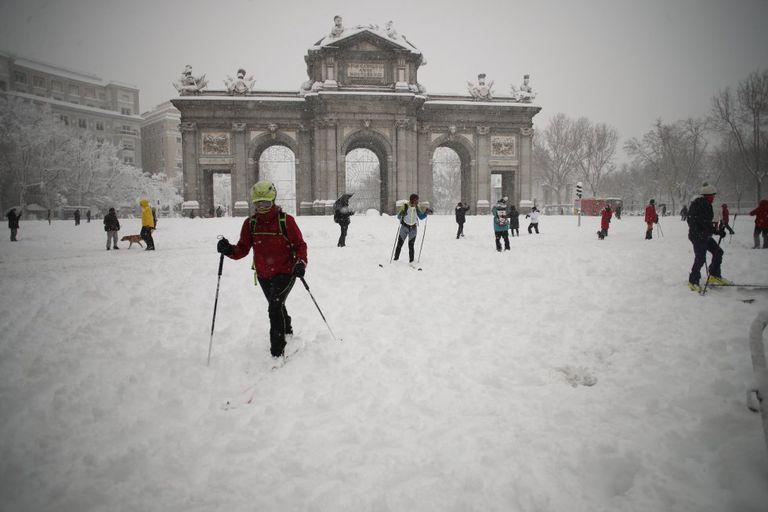 El temporal Filomena ha cubierto de blanco las calles y las carreteras, intransitables para los vehículos y conquistadas, seguramente por primera vez en la historia, por esquiadores, familias con sus trineos y tablas de snowboard, con palos de trekking, y por cientos de madrileños que han salido a pasear y a disfrutar de la nieve. En la imagen, esquiadores alrededor de la Puerta de Alcalá, en Madrid.