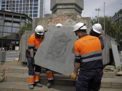 Varios trabajadores retiran un escudo del rey emérito de la plaza Cinc d'Oros de Barcelona, este sábado.