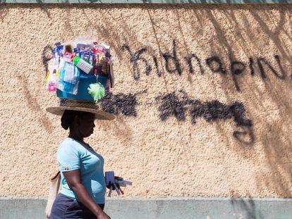 """Una mujer pasa junto a un grafiti en el que se lee """"Abajo los secuestros"""", el 16 de febrero en Puerto Príncipe (Haití)."""