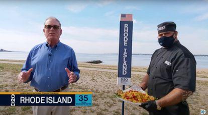 El demócrata de Rhode Island Joseph McNamara posa junto a un cocinero con un plato de calamares.