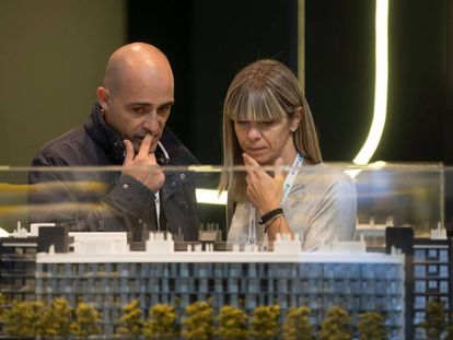 Dos visitantes al salón inmobiliario Barcelona Meeting Point (BMP) observan una maqueta.