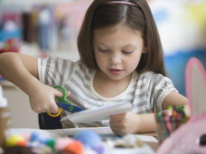Una niña hace manualidades en el colegio.