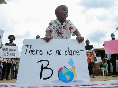 Un niño y otros jóvenes activistas  ugandeses contra el cambio climático se manifiestan en el barrio de Luzira de Kampala, Uganda, el 25 de septiembre de 2020.