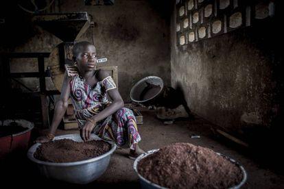 Una joven espera su turno para continuar moliendo el karité en la cooperativa de Fo-Bouré (Benín).