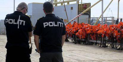 Dos policías, frente a un barco de Frontex que patrulla el Mediterráneo central.