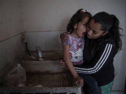 Valeria González y su hija Liz, que sufre discapacidad múltiple, en el lavadero donde se asean. Viven sin agua corriente en Ecatepec (México).