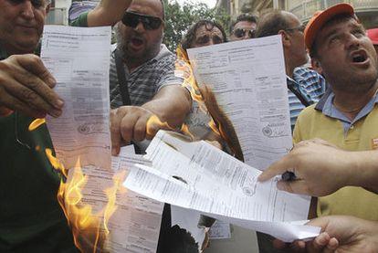 Funcionarios griegos protestan con la quema de liquidaciones de un impuesto.