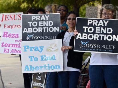 Manifestantes en contra del aborto sostienen carteles pro vida.