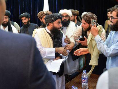 El portavoz talibán Zabihullah Mujahid abandona la sala de prensa este martes 17 de agosto mientras le sacan una foto. El líder afgano ha aprovechado la conferencia para quejarse de la censura de Facebook.