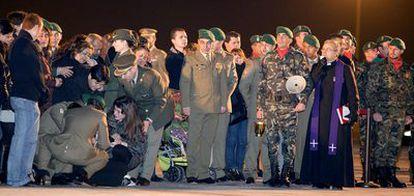 Varios militares atienden a la hermana del soldado fallecido, que se desplomó durante la recepción del féretro en el aeropuerto de Barcelona mientras un sacerdote rezaba un responso.