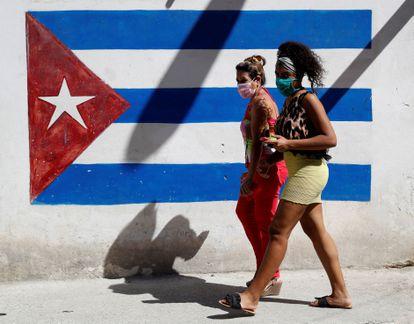 Dos mujeres caminan frente a un grafiti de la bandera cubana, este jueves en La Habana.