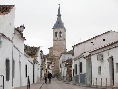 Dos hombres caminan por Torres de la Alameda en dirección a la iglesia.
