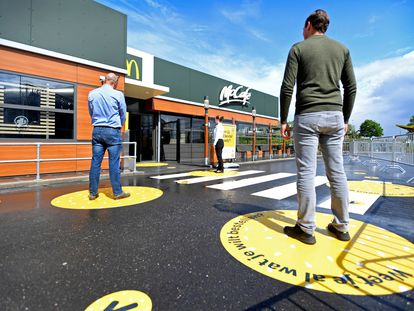 Clientes mantienen la distancia social recomendada para acceder a un McDonald's, en Holanda.