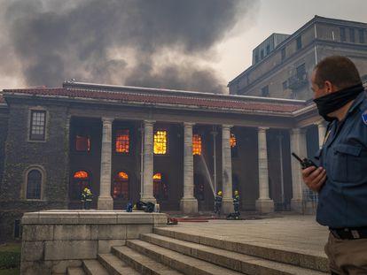 Bomberos tratan de apagar el fuego en la histórica biblioteca Jagger de la Universidad de Ciudad del Cabo, este domingo.