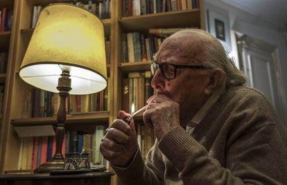 Andrea Camilleri se enciende un cigarrillo en la bilbioteca de su casa en Roma.