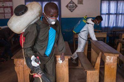 Trabajadores del Ministerio de Salud usan pesticida en una escuela de Andraisoro, Madagascar, para combatir la peste.