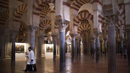 Un monaguillo bajo los arcos bicolor de la Mezquita de Córdoba.