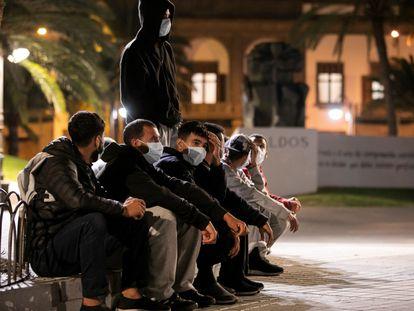 Un grupo de inmigrantes, sentados frente a la Delegación del Gobierno en Las Palmas de Gran Canaria en la noche del 17 de noviembre.