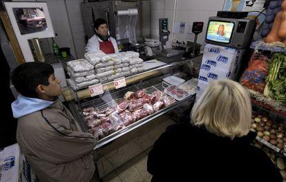 Un empleado y dos clientes en una carnicería en Buenos Aires observan un discurso de Cristina Fernández.