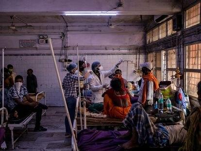El equipo médico del hospital Lal Nehru de Laldawar atiende a un paciente enfermo de covid-19 en la sala de urgencias del centro sanitario en julio de 2020.