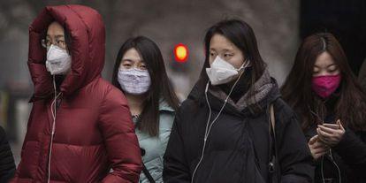 Un grupo de pekinesas usan máscaras para protegerse de la polución.