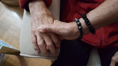 Una mujer coge la mano de su marido, con Alzhéimer.