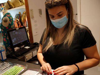 La encargada de una tienda de ropa ordena mascarillas en el mostrador de su local en Barcelona.