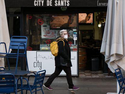 Una mujer pasa ante la terraza de un bar en una calle de Barcelona, el pasado febrero.