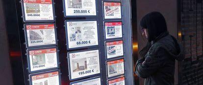 Escaparate con anuncios de venta de viviendas.