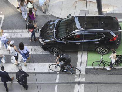 Una calle de Toronto (Canada) con peatones, ciclistas y coches.