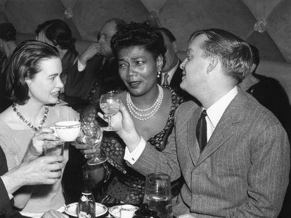 Truman Capote charla con la artista Gloria Vanderbilt (izquierda) y la cantante Pearl Bailey en un club de Nueva York en 1955.