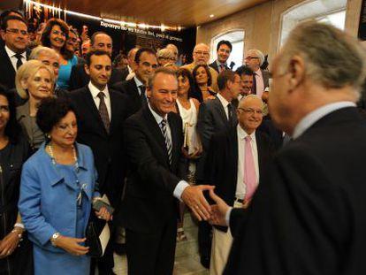 Alberto Fabra, presidente de la Generalitat, tiende la mano a Rafael Blasco ante los miembros del grupo parlamentario del PP en las Cortes.