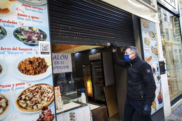 El encargado de un bar del centro de Valencia cierra las puertas, el martes.