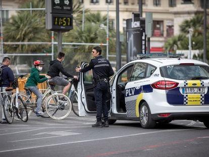 La policía de Valencia advierte a unos paseantes de que tienen que quedarse en casa. En vídeo, Pedro Sánchez responde a la pregunta de cómo se garantizará que los ciudadanos cumplan las restricciones.