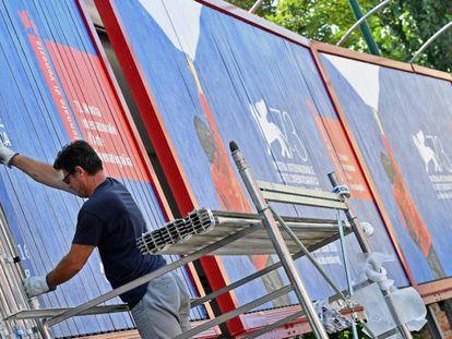 Un trabajador coloca varios carteles de la 73ª edición del festival de Venecia.