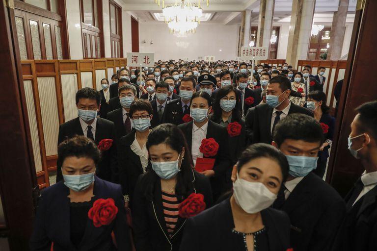 Un grupo de personas con mascarilla asiste a un evento para celebrar el trabajo de los héroes de la lucha contra la covid en Pekín, el pasado 8 de septiembre.