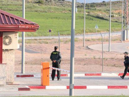 Un vigilante de seguridad privada junto a dos guardias civiles, en la zona de acceso a la cárcel de Villena (Alicante), el 2 de agosto.