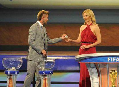 David Beckham entrega una bola a Charlize Theron, presentadora del acto; abajo, a la derecha, el trofeo de campeón del mundo.