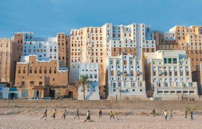 Jóvenes juegan en la arena ante varios edificios de la ciudad de Shibam, al oeste de la gobernación yemení de Hadramaut.