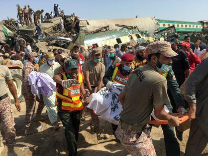 Miembros de los equipos de rescate trasladan el cuerpo de una de las víctimas de la colisión de dos trenes en Ghotki, Pakistán, este lunes.