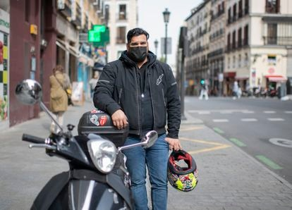 Marco Pérez, on a Madrid street with the motorcycle on which he distributes food.