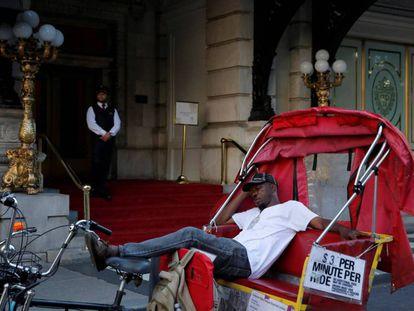 Un conductor de bicitaxi espera clientes en la puerta del Hotel Plaza de Nueva York