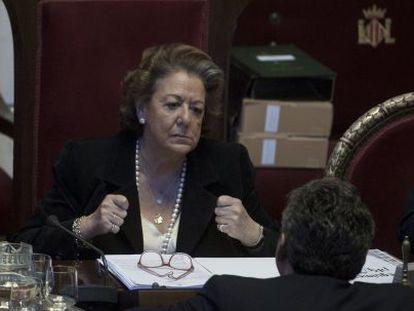 La alcaldesa de Valencia, Rita Barberá, habla con un concejal durante el pleno.