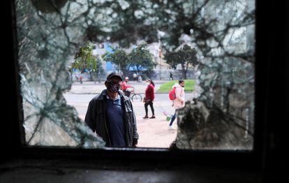 Un hombre mira a través de una ventana rota de una comisaría de policía destrozada después de una protesta en Bogotá el 5 de mayo.