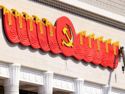 Un trabajador realiza labores en el emblema del Partido Comunista Chino en Pekín.