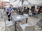 Un camarero desinfecta una mesa después de su uso en una céntrica terraza madrileña en el primer día de la Fase 1, cuando se reabren al público las terrazas al aire libre de los establecimientos de hostelería y restauración limitándose al 50\% de las mesas y garantizándose una distancia de 2 metros entre mesas o agrupaciones de mesas. En Madrid (España), a 25 de mayo de 2020.  Joaquin Corchero / Europa Press 25/05/2020